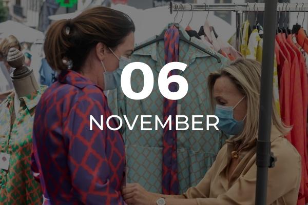 Una mujer se prueba un abrigo ayudada por una dependienta en el mercadillo de Salesas