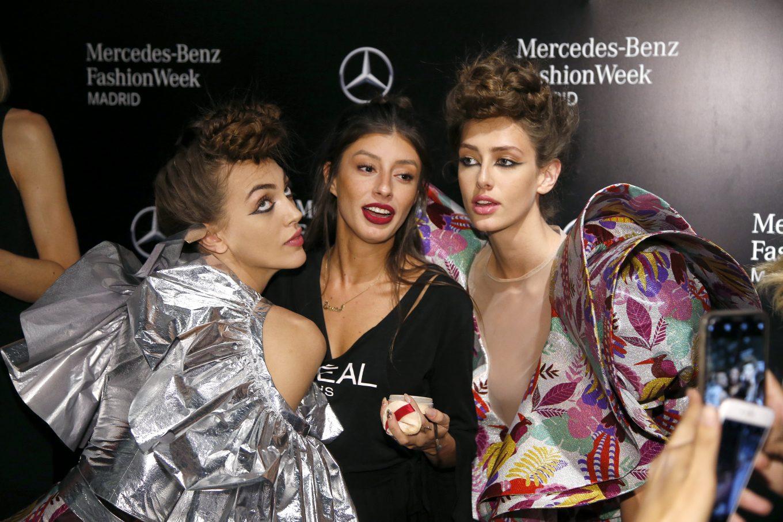 Modelos rodean a maquilladora