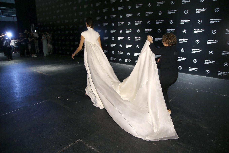 Modelo con traje de novia y mujer llevando la cola