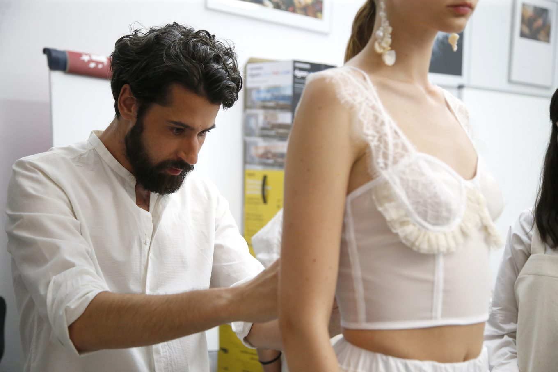 Diseñador ajusta traje de modelo