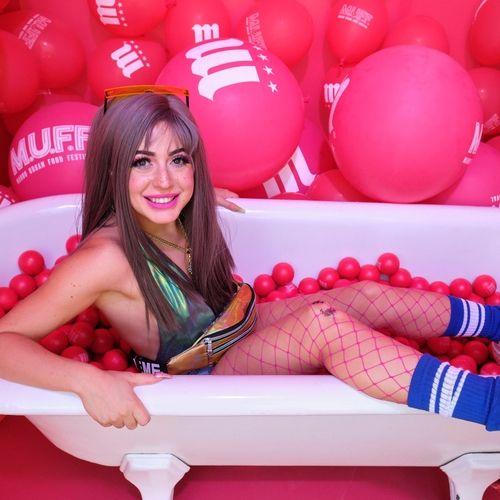 Modelo dentro de bañera con pelotas de plástico y globos en las paredes