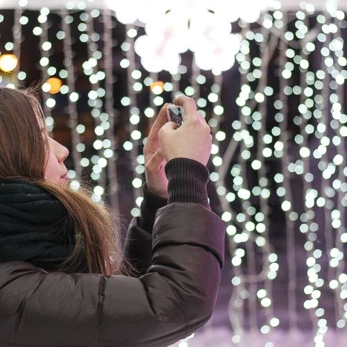 Mujer con abrigo y bufanda sujetando camara de fotos