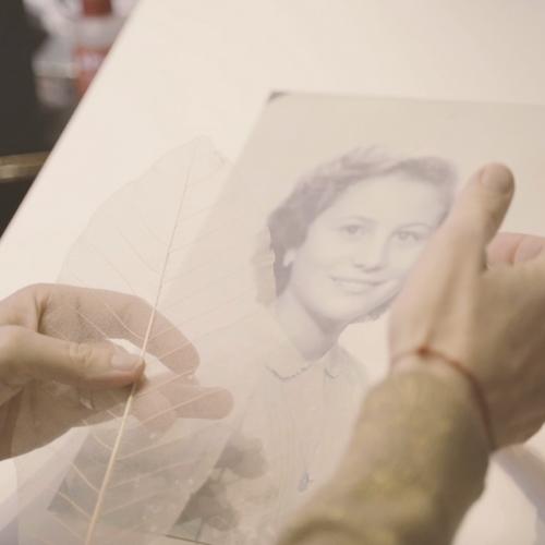 Manos manejando hoja de seda con fotografía de mujer en segundo plano