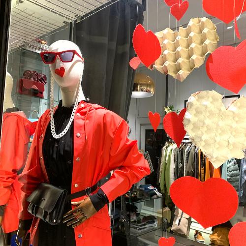 Maniquí en escaparate de tienda de moda decorado con corazones