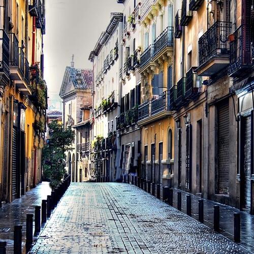 Calle con suelo mojado y desierta en barrio de las letras