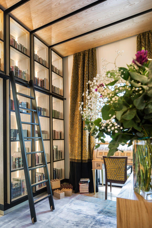 Biblioteca con escalera y florero en primer plano