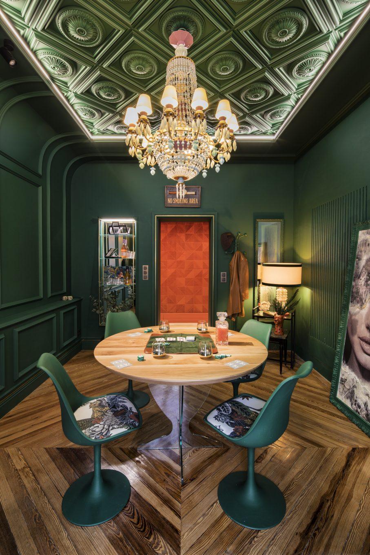 Sala de juegos con mesa, tapete con cartas y sillas