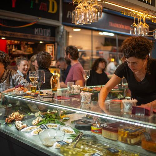 Mujer atendiendo barra de bar con clientes hablando entre sí