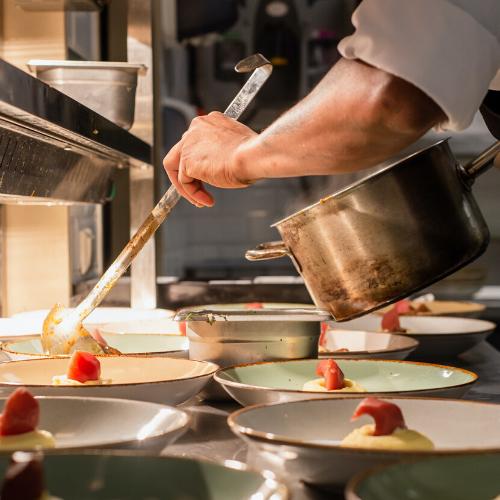 Cocinero sirviendo comida en platos desde cazuela