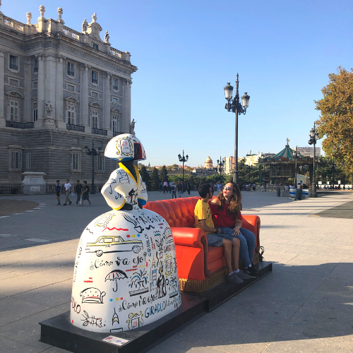 Menina con sofá y personas sentadas en él en Plaza de Oriente, Madrid