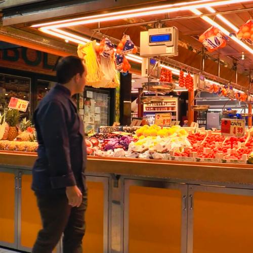 Hombre pasando por delante de puesto de frutería en mercado