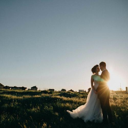 Pareja de recien casados en campo al atardecer