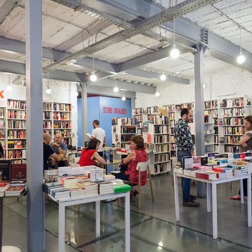 Interior de librería con gente, estanterías y expositor