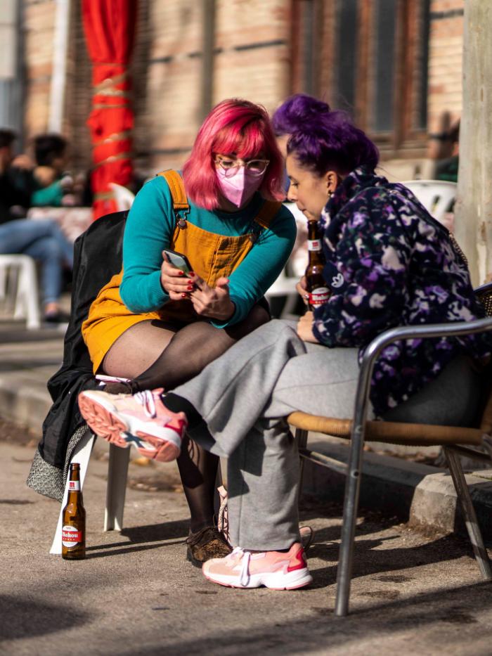 Dos amigas miran un teléfono móvil