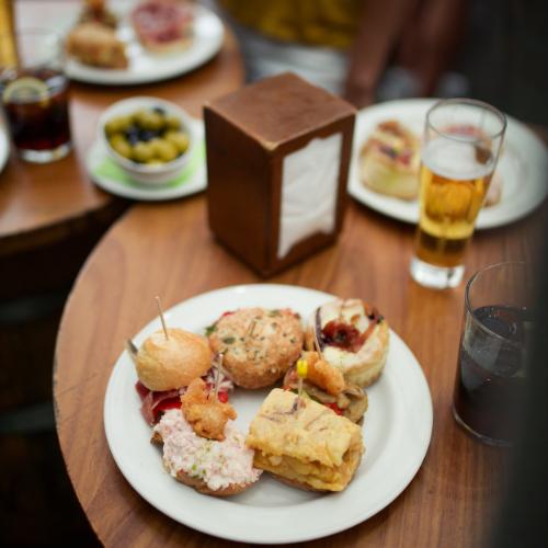 Mesa con un plato de tapas y cervezas