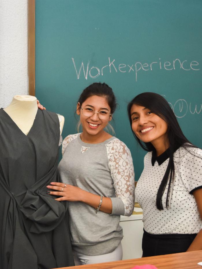 Alumnas de costura junto a un maniquí