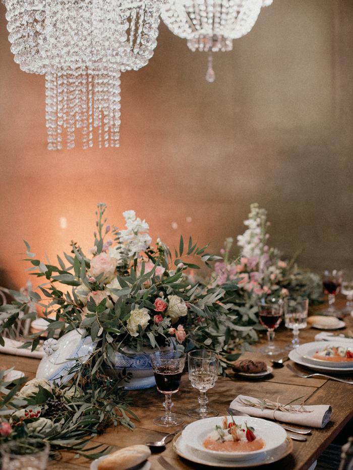 Mesa con flores y platos con salmorejo