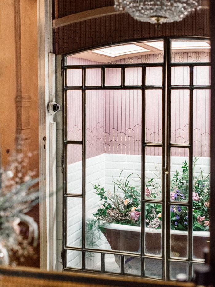 Bañera llena de flores vista a través de una ventana