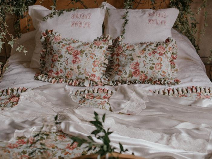 Cama con sábanas blancas y cojines florales