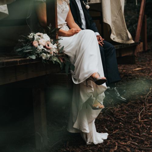 Vestido de novia, ramo de flores y zapatos de tacón plateados