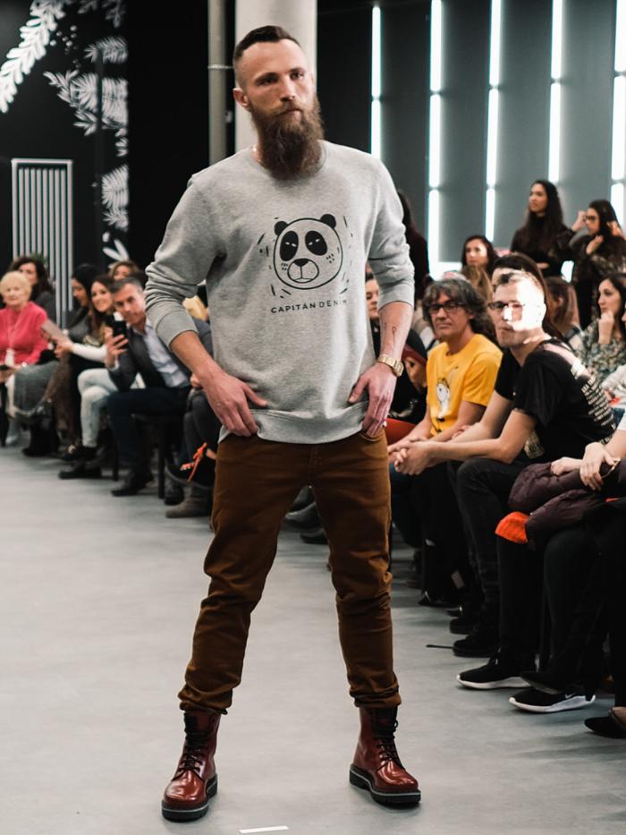 Hombre con sudadera gris y pantalones marrones