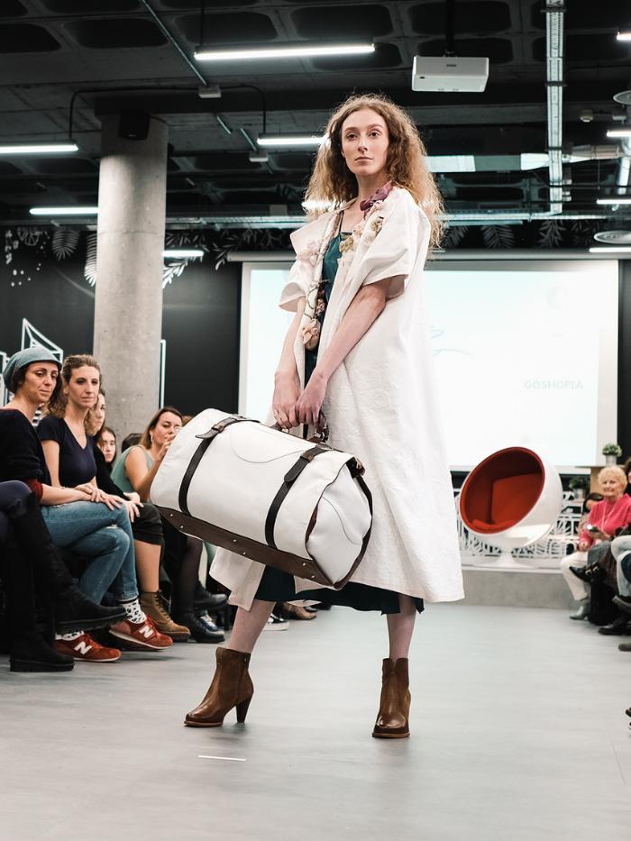 Mujer vestida de blanco con bolsa de viaje blanca