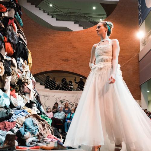 Mujer vestida de blanco observa un montón de ropa