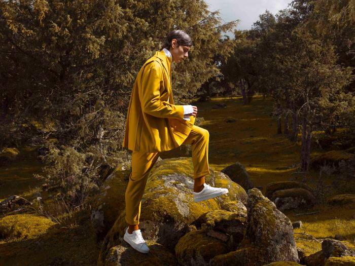 Hombre vestido con un traje mostaza en un bosque