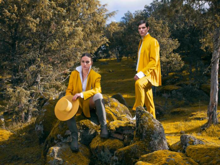 Mujer y hombre vestidos con trajes mostaza en un bosque