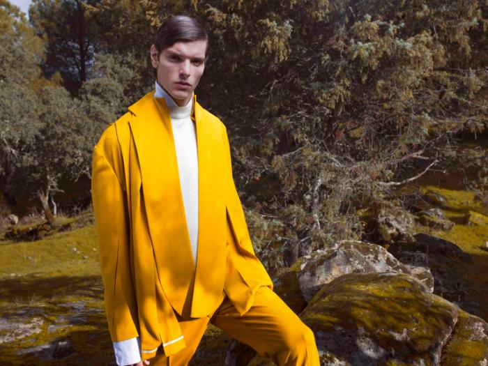 Hombre vestido con traje mostaza en un bosque