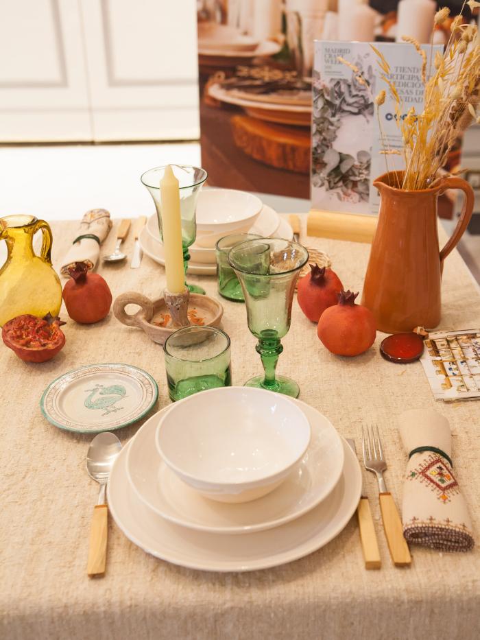 Mesa con vajilla blanca y copas de vidrio verde