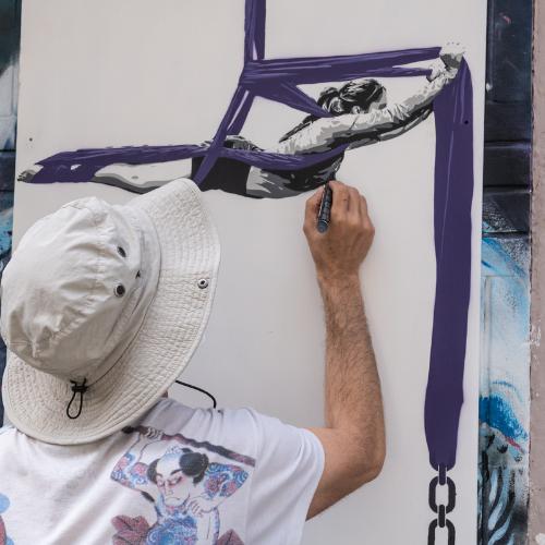 Artista callejero pintando un mural