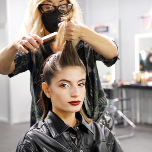 Una peluquera peina a una modelo en el backstage de MBFW Madrid